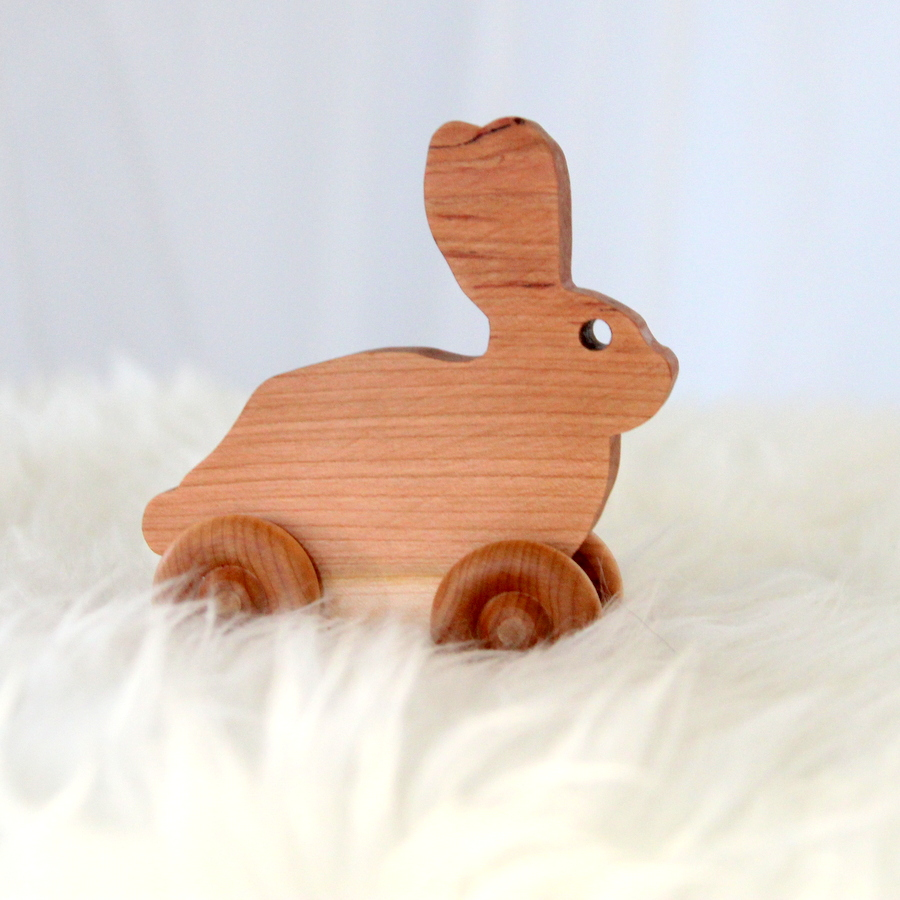 snow bunny themed first birthday party favors- rolling wooden bunnies by simple.great on etsy