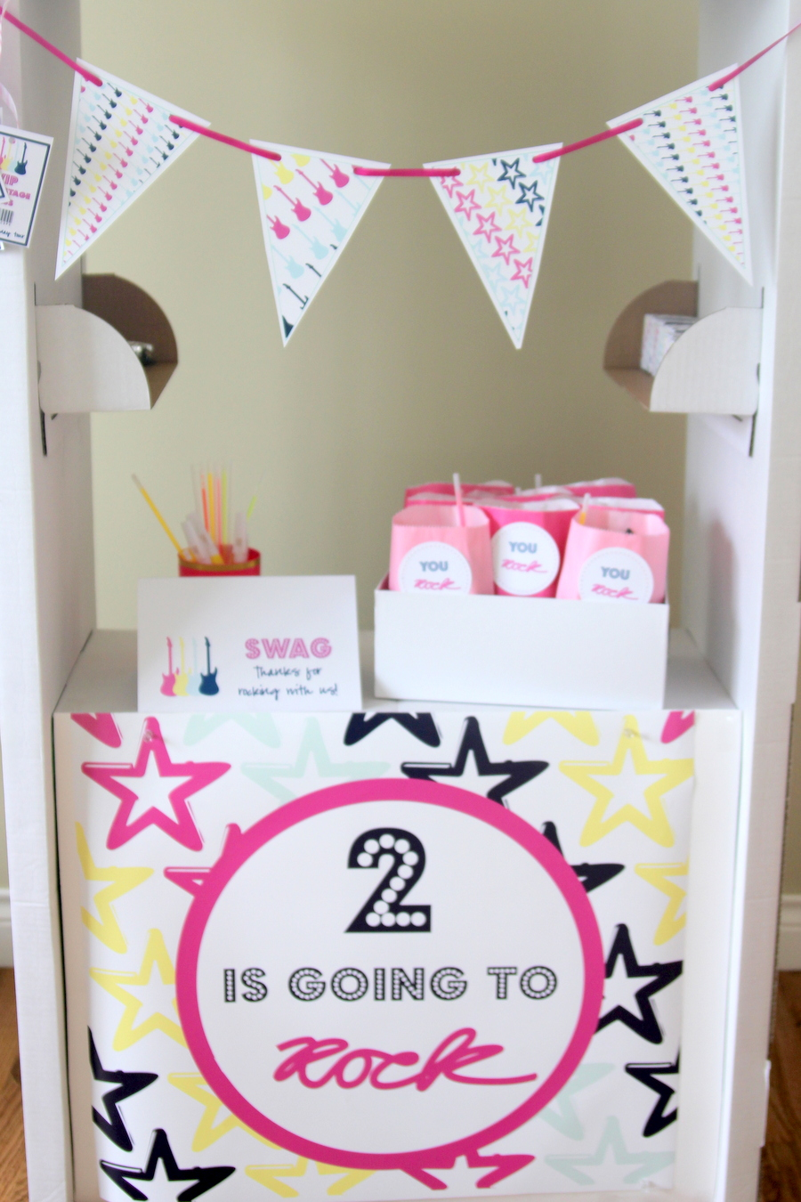 Time to party like a rock star! This sweet rock star birthday party includes all sorts of party ideas- like this cute swag booth made from a $15 IKEA cardboard market!