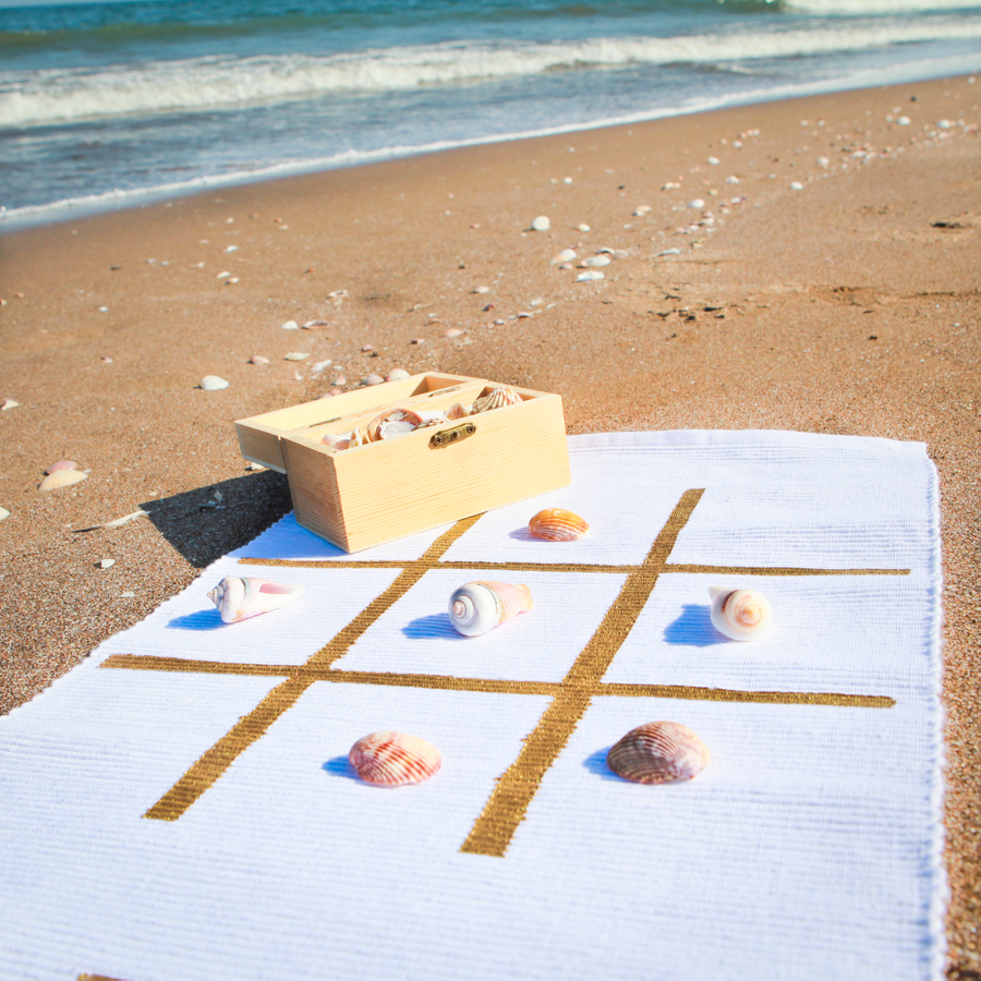 Outdoor game mat to take with you to the beach or park- this DIY outdoor classic game board is the perfect way to put your shell collection to good use