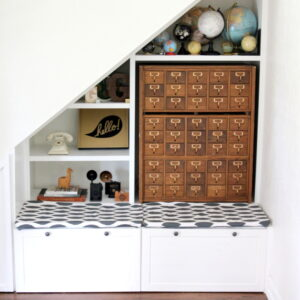 The perfect use for the space under the stairs- book shelves, a bench, drawers and even a little closet