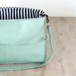 How to make your own messenger bag (with a padded laptop pocket!). This one is a diaper bag, but it'd make a great travel bag or laptop bag...
